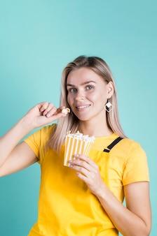 Jolie femme mangeant du maïs soufflé moyen