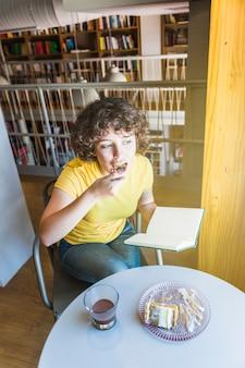 Jolie femme mangeant un gâteau dans la bibliothèque
