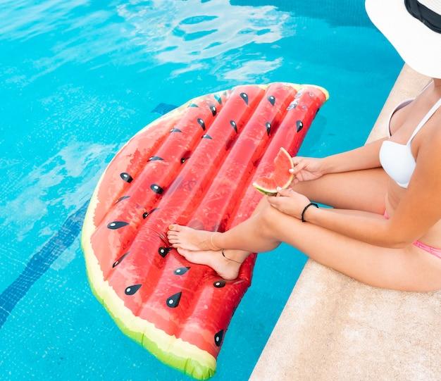 Jolie femme mangeant une pastèque, sur un tapis dans la piscine