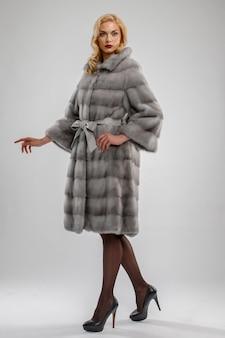 Jolie femme en manteau de fourrure gris.