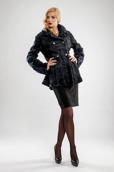 Jolie femme en manteau de fourrure noir. maquillage parfait, lèvres rouges et yeux bleus.