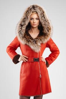 Jolie femme en manteau de peau de mouton rouge posant avec capuche en fourrure sur la tête