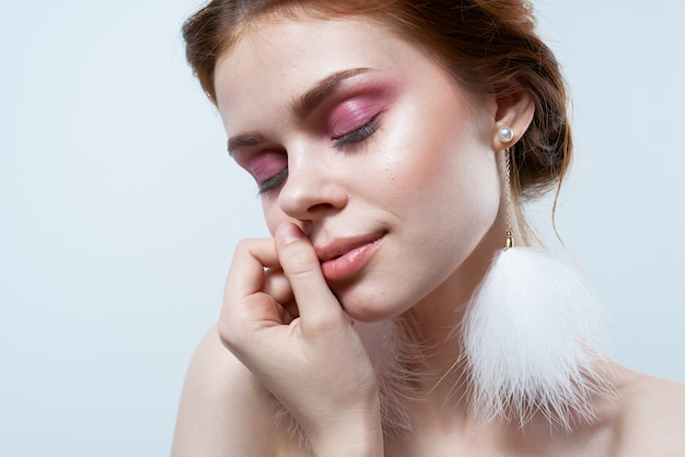 Jolie femme maquillage lumineux boucles d'oreilles moelleuses bijoux épaules nues peau claire.