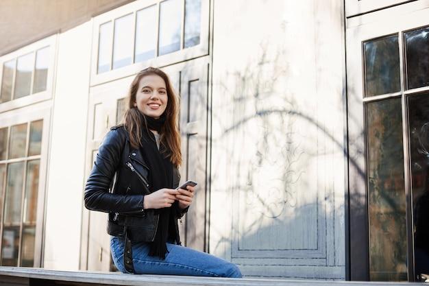Jolie femme marchant en ville, assis près d'un café, riant d'un mec drôle qui essaie de l'impressionner, tenant un smartphone.