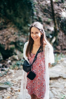 Jolie femme marche dans le parc en se présentant à la caméra.