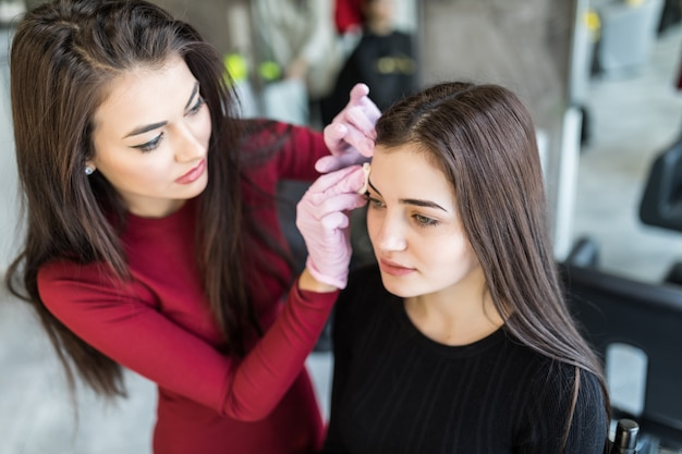 Jolie femme master faisant maquillage professionnel de jeune femme