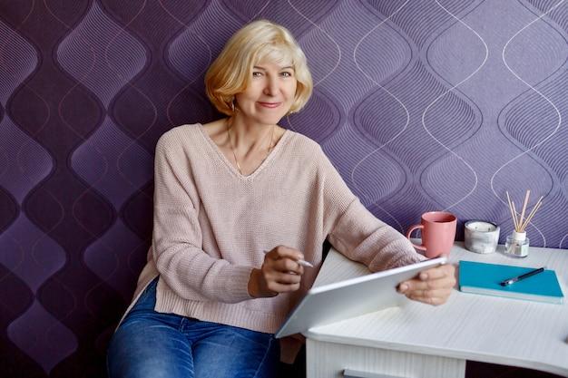 Jolie femme mature blonde à l'aide de tablette