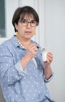 Jolie femme mature manger du yaourt à la maison
