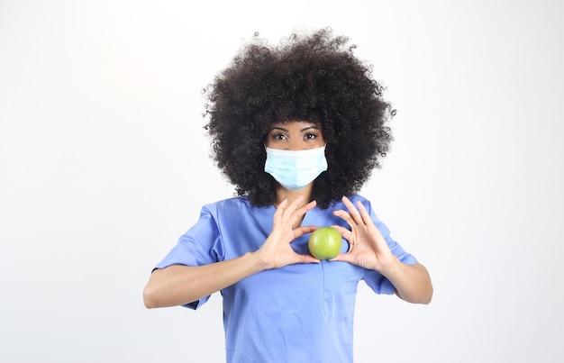 Jolie femme médecin afro, avec une pomme verte, fond blanc