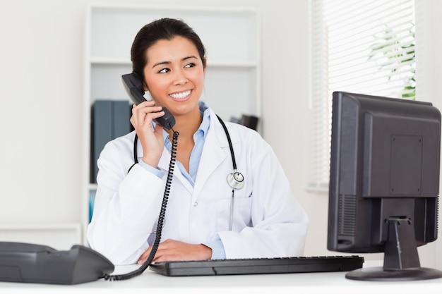 Jolie femme médecin au téléphone en position assise
