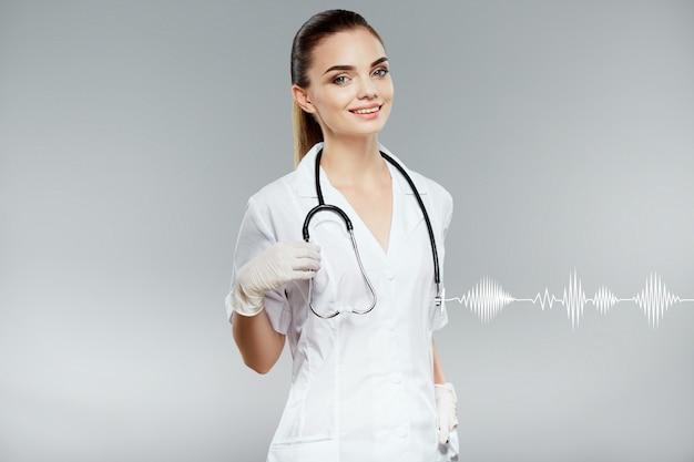 Jolie femme médecin aux cheveux bruns et maquillage nu portant une robe médicale blanche et des stéthoscopes à fond gris, concept de soins de santé et de pharmacologie, fille sur uniforme blanc.