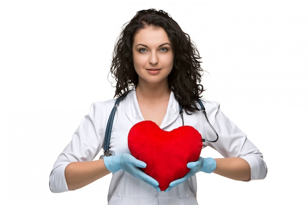 Jolie femme médecin tenant un coeur rouge