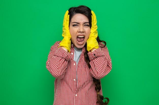 Jolie femme de ménage caucasienne agacée avec des gants en caoutchouc couvrant ses oreilles et
