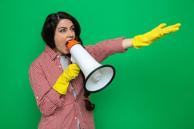 Jolie femme de ménage caucasienne agacée avec des gants en caoutchouc tenant un haut-parleur regardant et pointant sur le côté