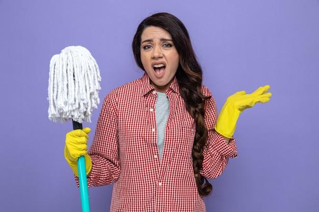 Jolie femme de ménage caucasienne mécontente avec des gants en caoutchouc tenant une vadrouille et gardant la main ouverte