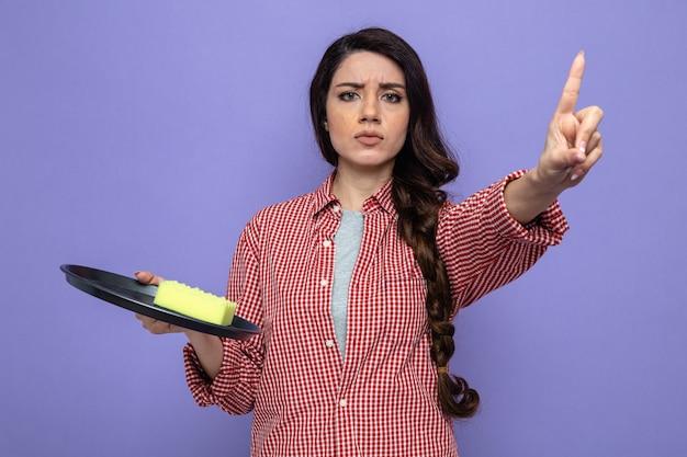 Jolie femme de ménage caucasienne sérieuse tenant une éponge sur une assiette et pointant vers le haut
