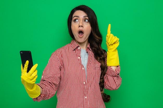 Jolie femme de ménage caucasienne surprise avec des gants en caoutchouc tenant un téléphone et pointant vers le haut en regardant de côté