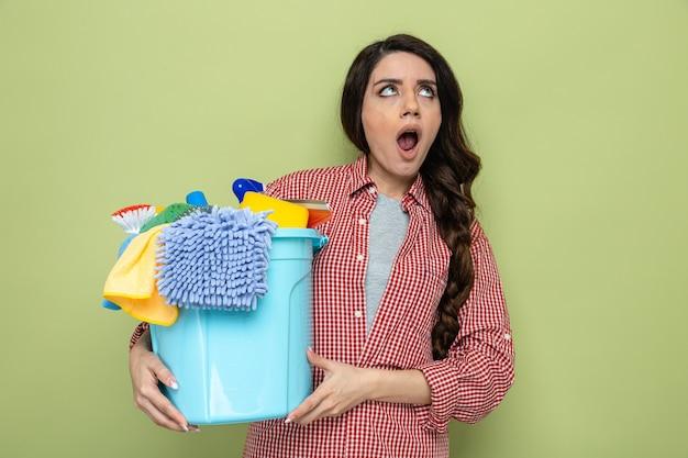 Jolie femme de ménage caucasienne surprise tenant du matériel de nettoyage et levant les yeux