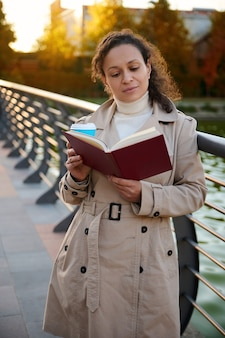 Jolie femme métisse profitant de son week-end en plein air, se reposant dans le parc de la ville par une belle journée ensoleillée d'automne et lisant un livre et buvant du café. mode de vie, activité de loisirs, repos des gadgets