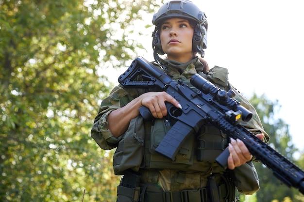 Jolie femme militaire courageuse avec une arme à feu dans la forêt, survie dans la forêt sauvage
