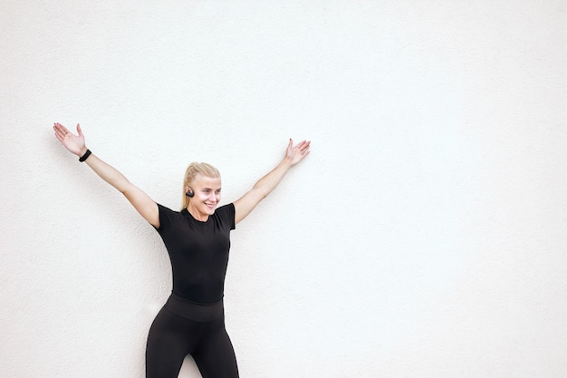 Jolie femme mince joyeuse portant des vêtements de sport noirs, écoutant de la musique et s'étirant après l'entraînement.