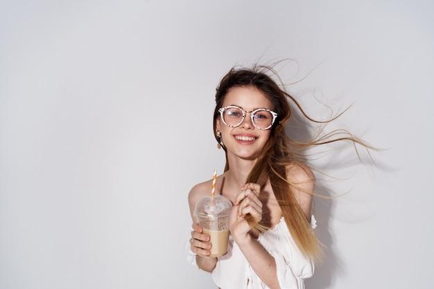 Jolie femme à la mode lunettes décoration sourire verre avec fond clair de charme de boisson. photo de haute qualité