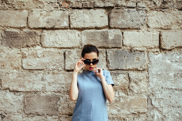 Jolie femme de mode en robe bleue avec des lunettes de soleil posant près du mur blanc