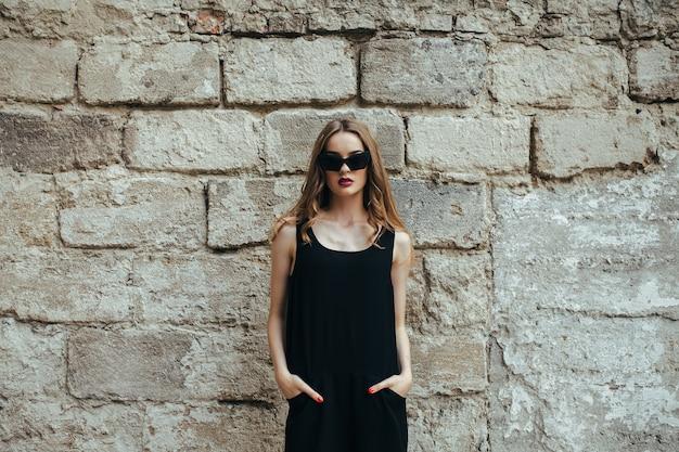 Jolie femme de mode en robe noire avec des lunettes de soleil posant près du mur blanc