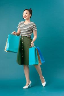 Une jolie femme à la mode tenant des sacs à provisions en papier coloré