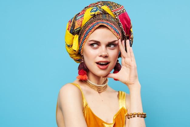 Jolie femme multicolore décoration turban mode close-up fond bleu.