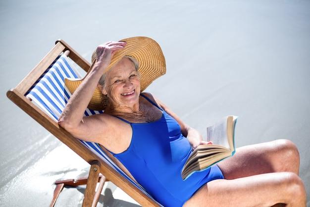 Jolie femme mûre lisant un livre allongé sur une chaise longue