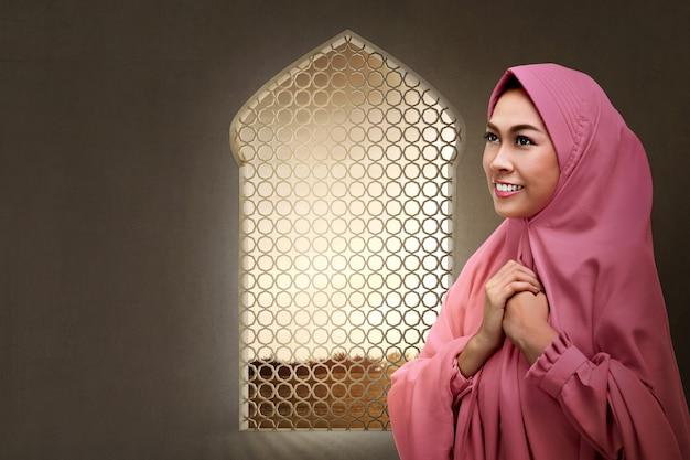 Jolie femme musulmane asiatique priant dieu