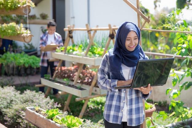 Jolie femme musulmane avec ordinateur portable à la ferme