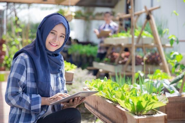 Jolie femme musulmane avec tablette à la ferme