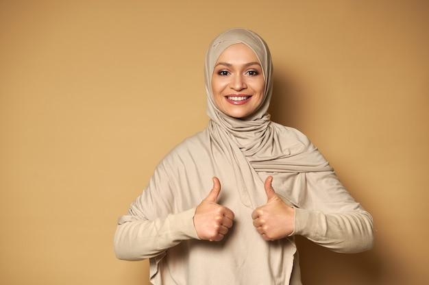 Jolie femme musulmane avec tête couverte en hijab montre les pouces vers le haut et sourit avec un sourire à pleines dents sur une surface beige avec copie espace