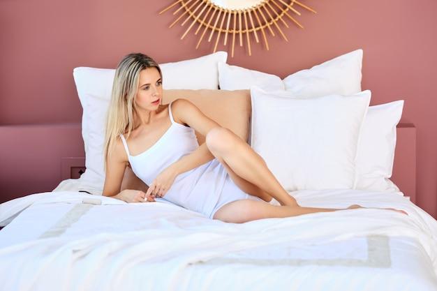 Jolie femme négligente au lit en journée ensoleillée