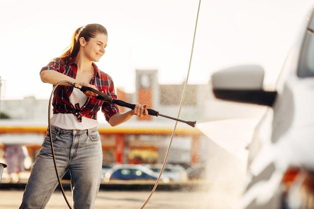 Jolie femme nettoie les roues de la voiture avec un pistolet à eau