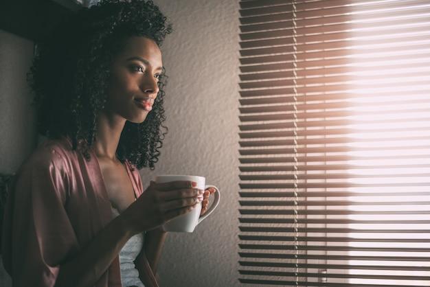 Jolie femme noire assise à la fenêtre avec une tasse de café