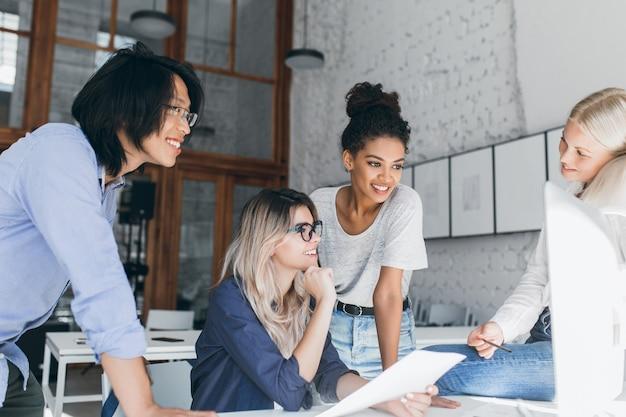 Jolie femme noire aux cheveux courts plaisantant avec des amis sur leur lieu de travail pendant la pause