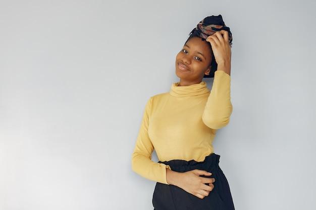 Jolie femme noire debout sur un mur blanc