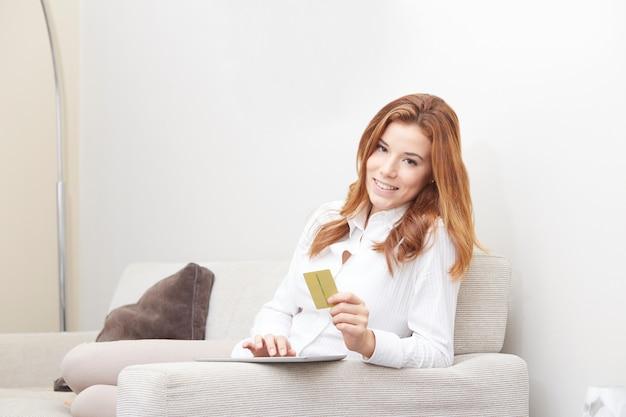 Jolie femme avec ordinateur portable sur le canapé
