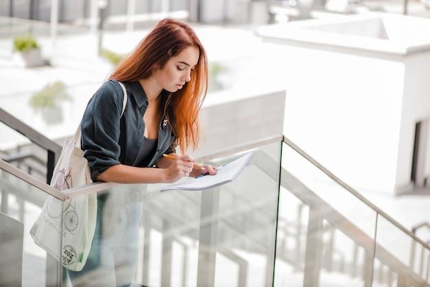 Jolie femme avec des papiers sur les escaliers seul