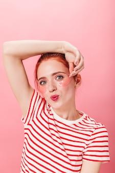 Jolie femme avec des patchs oculaires posant avec l'expression du visage qui s'embrasse. photo de studio d'une fille au gingembre portant un t-shirt rayé.