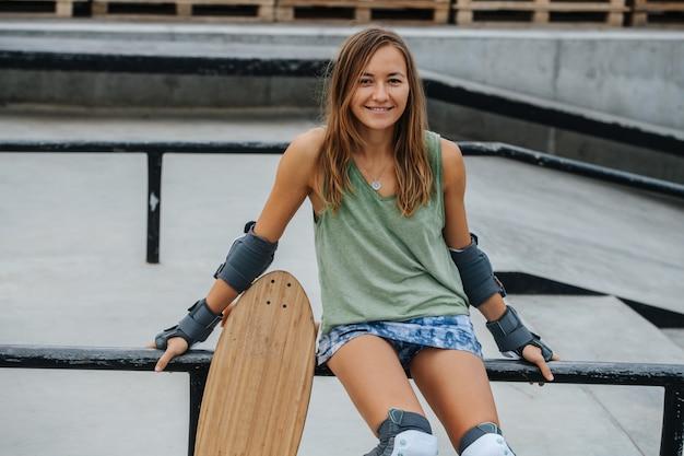 Jolie femme patineuse assise sur une balustrade au skatepark avec pavage en béton. vue frontale, portrait, regardant la caméra.