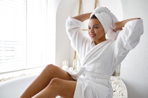 Jolie femme en peignoir assis près de la baignoire. personne de sexe féminin dans la baignoire, soins de beauté et de santé au spa, traitement de bien-être dans la salle de bain, cailloux et bougies sur fond