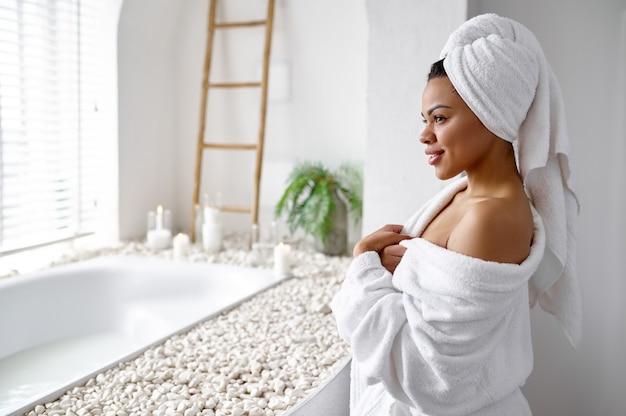 Jolie femme en peignoir assis près de la baignoire. personne de sexe féminin dans la baignoire, soins de beauté et de santé au spa, traitement de bien-être dans la salle de bain