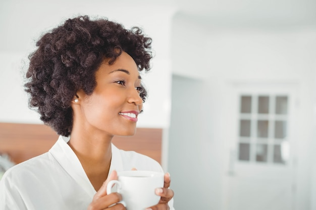 Jolie femme en peignoir buvant du café dans la cuisine à la maison