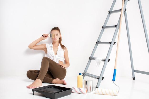 Jolie femme peinture mur dans sa maison. belle femme tenant un pinceau