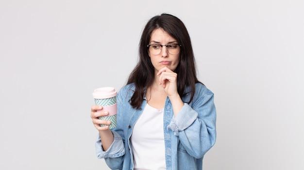 Jolie femme pensant, se sentant dubitative et confuse et tenant un café à emporter