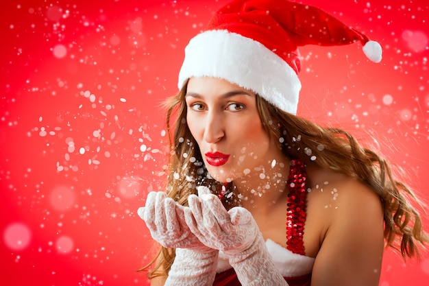 Jolie femme en père noël soufflant de la neige